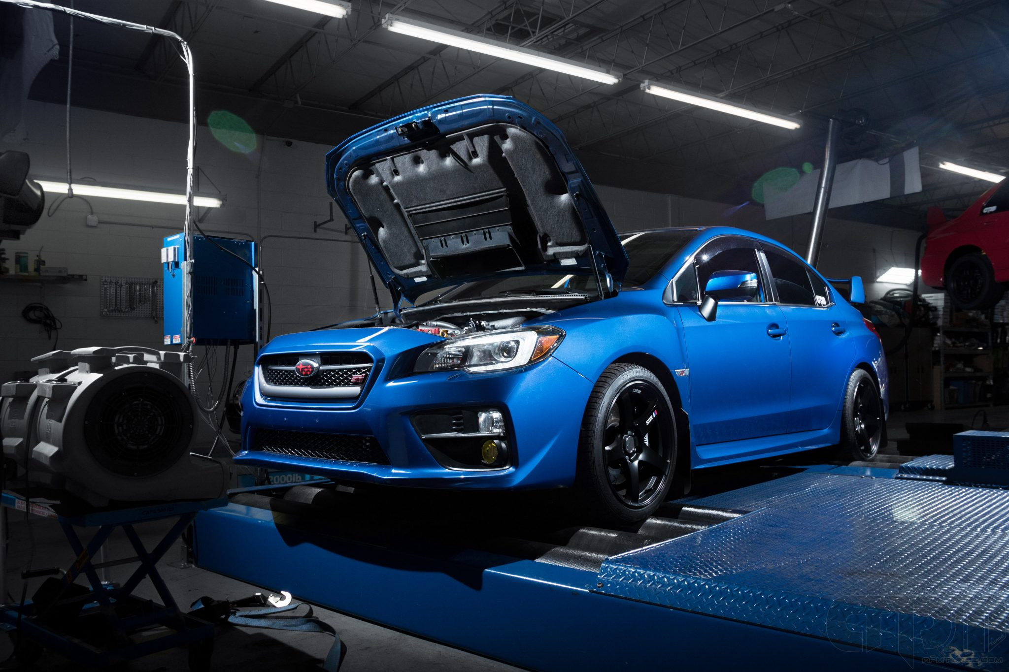 Dramatically lit Blue STI getting tuned on our Blue Nissan GT-R rolling while getting custom pro tuned on our Mustang AWD 4WD Dynamometer Dyno