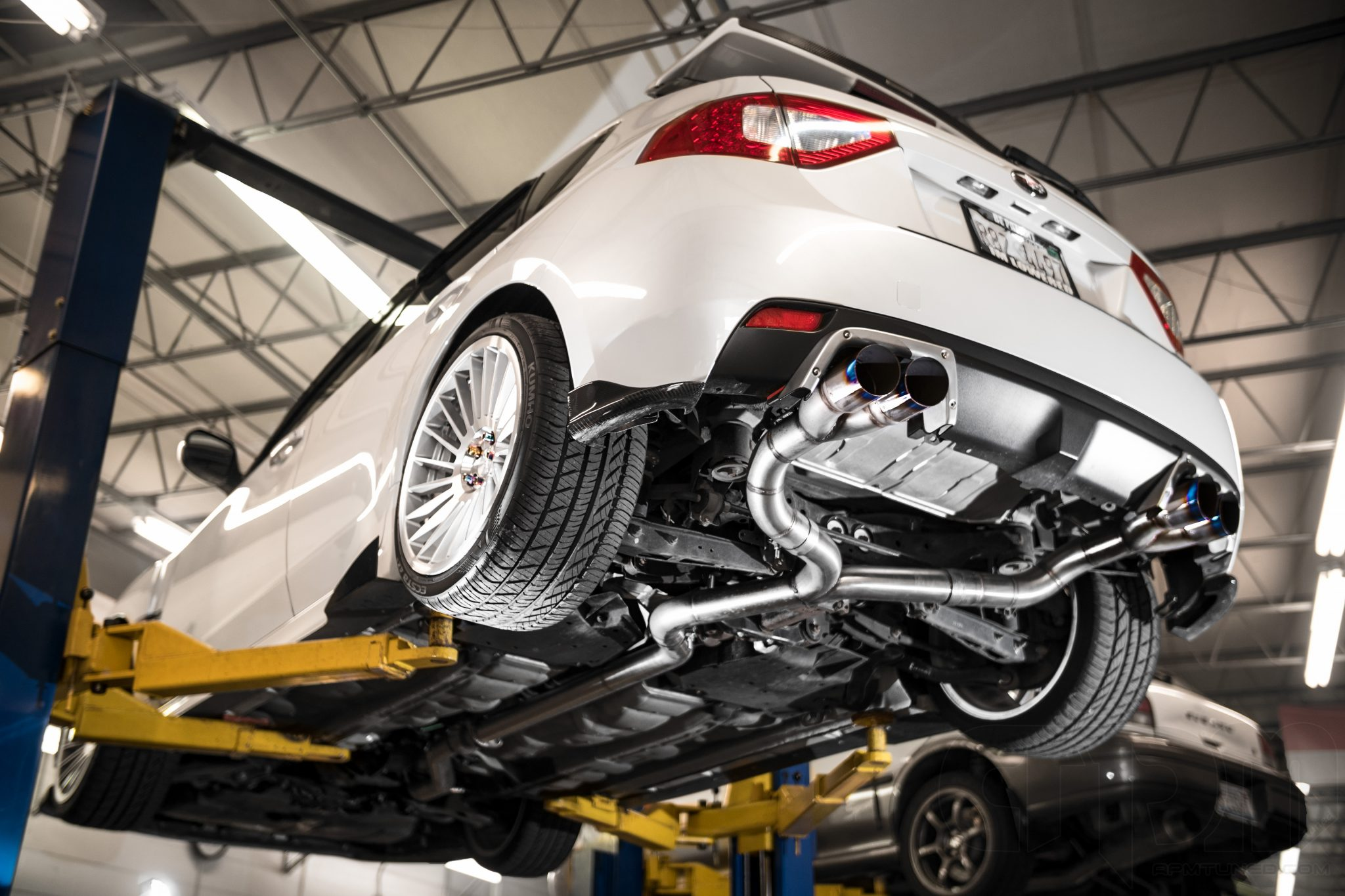 Custom Fabricated Exhaust on a white Subaru WRX Hatchback