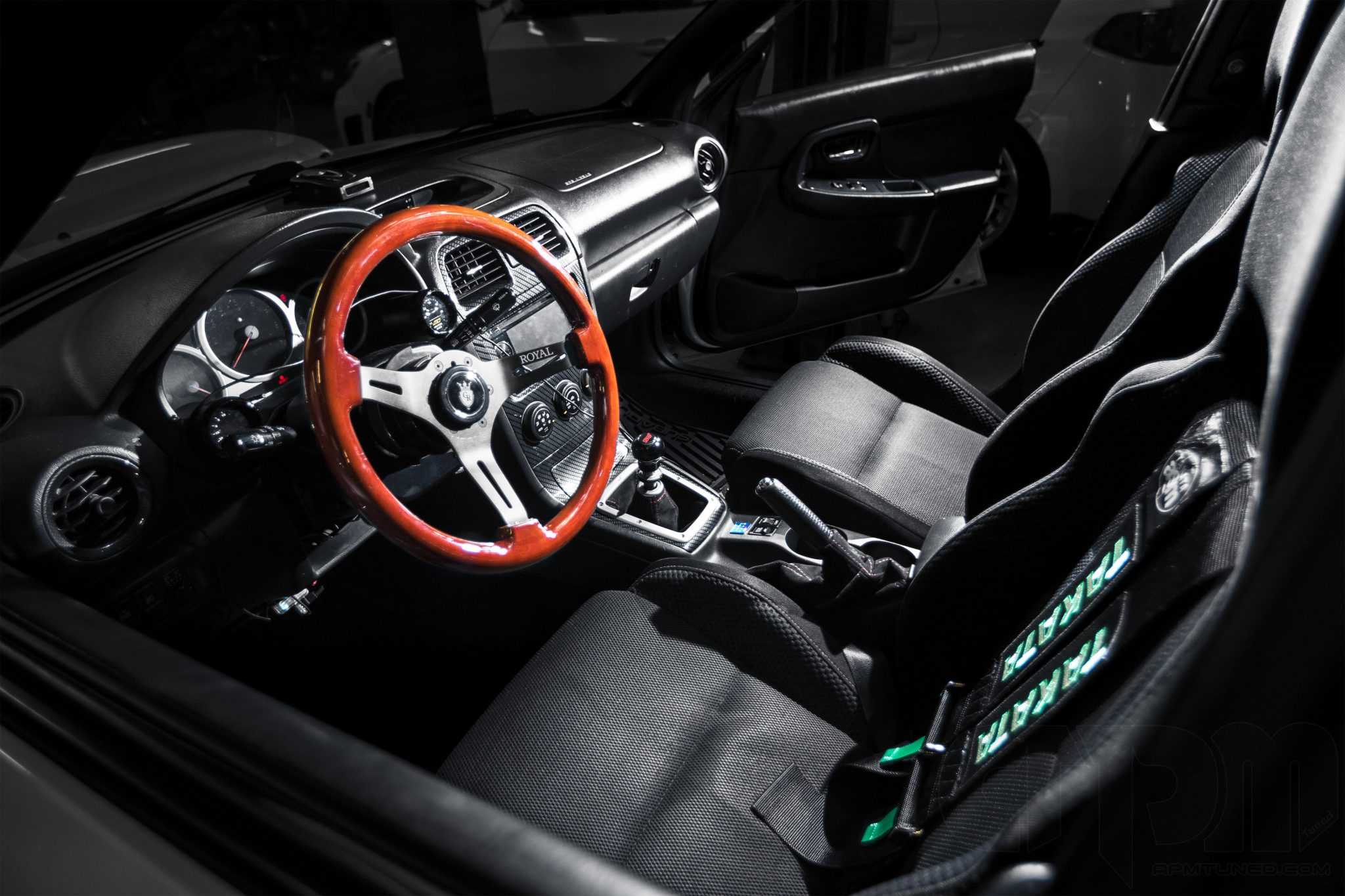 Interior shot of an STi equipped with Takata racing harness, Royal Steering Wheel, Boost and Oil Gauge