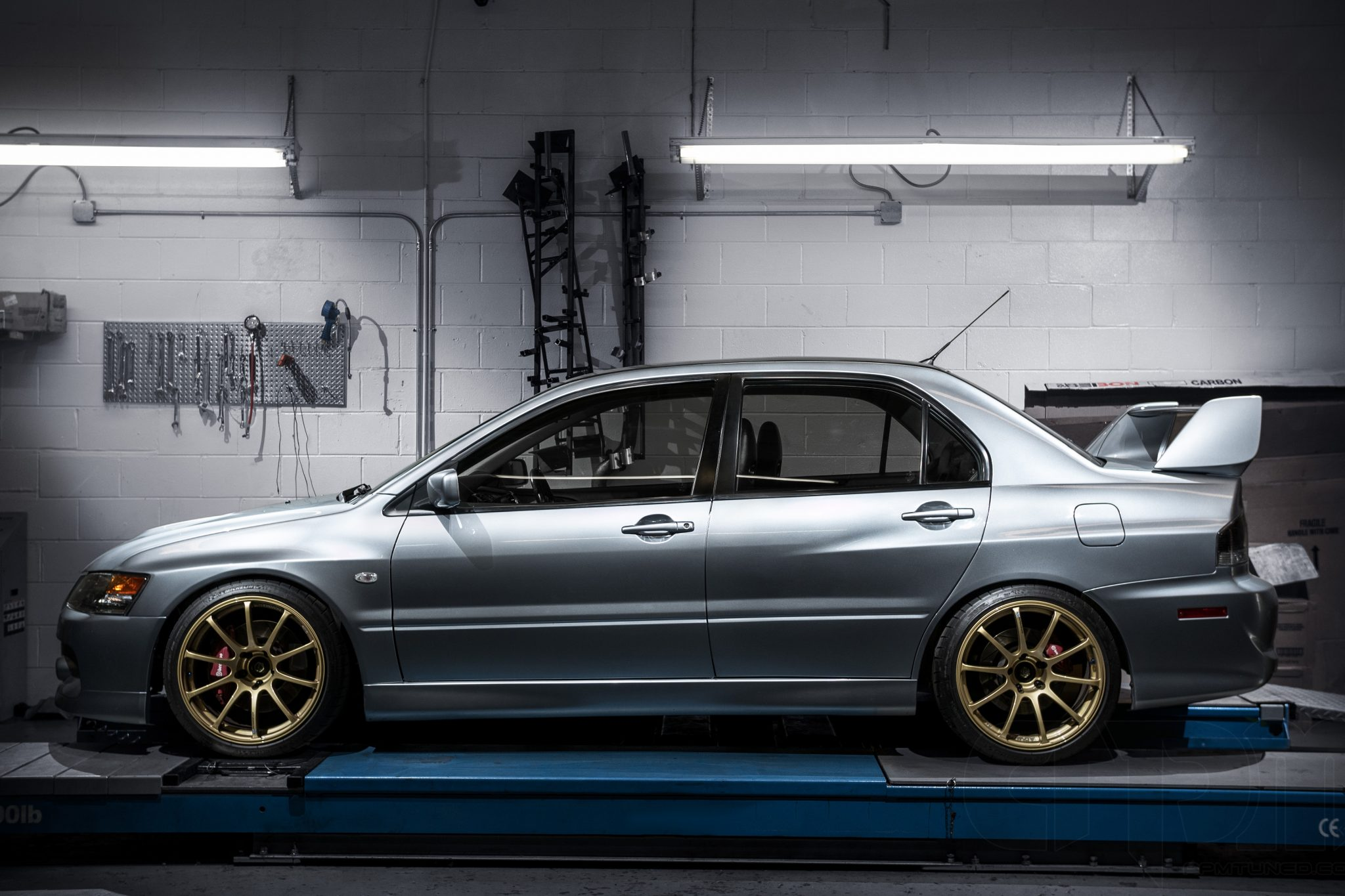 Silver Mitsubishi Evo with gold wheels and red brembo brakes sitting on our alignment rack