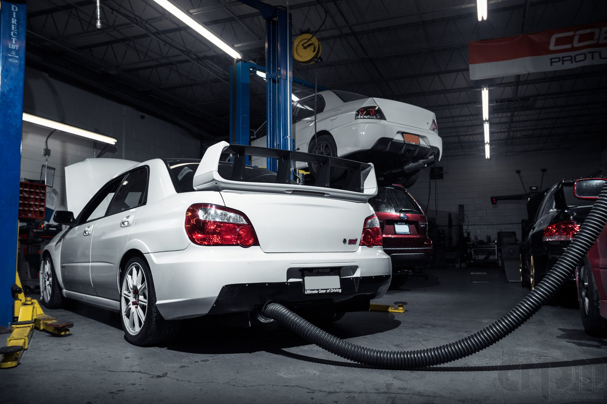 White Subaru STi getting tested inside of the shop, pipe attached to exhaust pipe to remove fumes