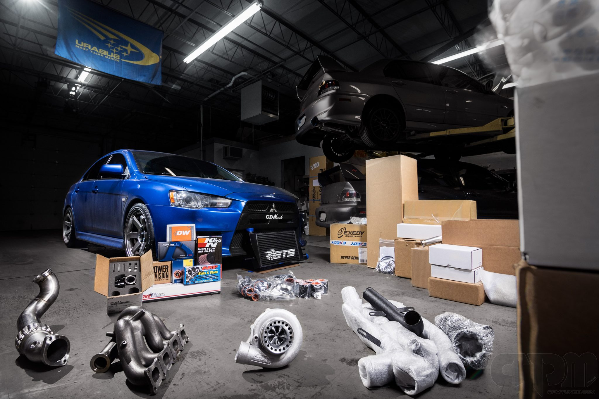 Blue Mitsubishi in our shop with dozens of brand new parts infront of it, ready to be installed. Some but not all included are a brand new turbocharger, headers, uppipe, downpipe, intake, exedy clutch, fuel pump, intercooler, tial BOV and more