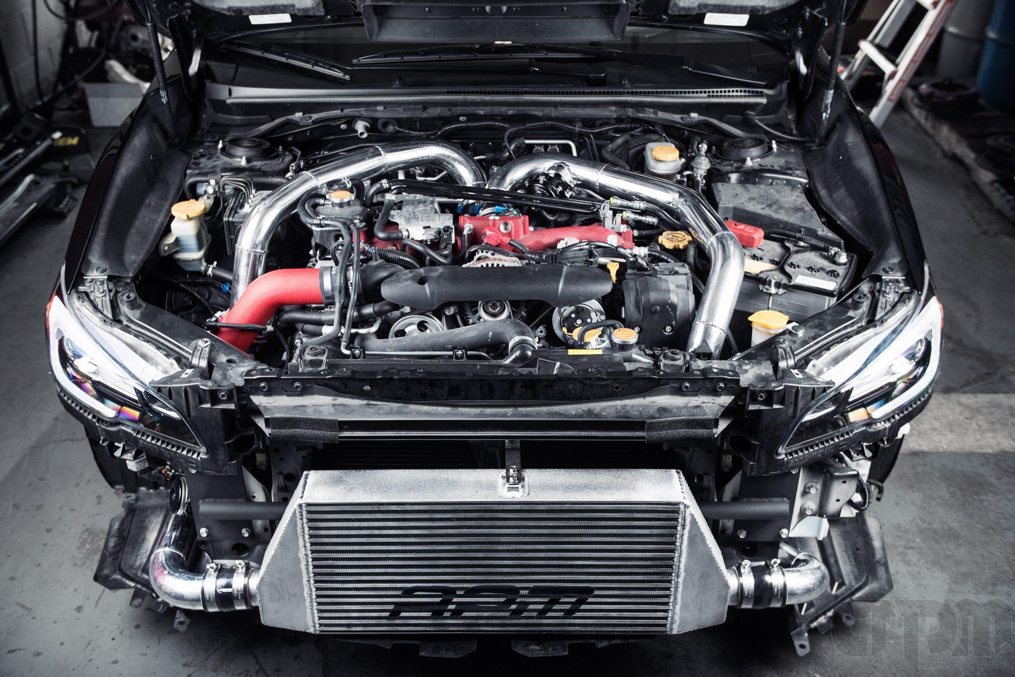 Black Subaru STi Engine bay with custom installed APM Intercooler