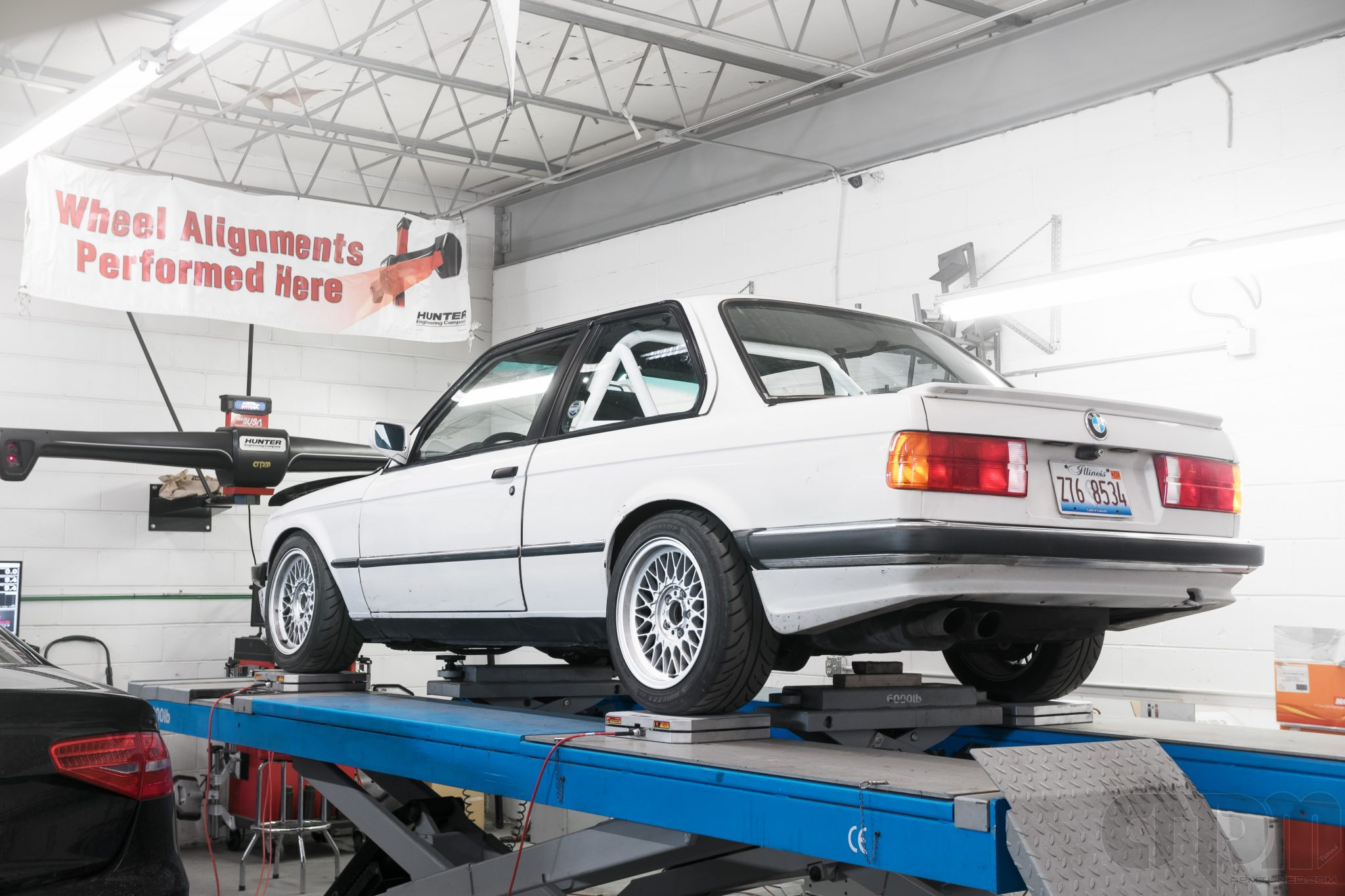 White E30 BMW Track car getting corner balanced on our alignment rack